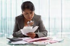 Asiatische Geschäftsfrau, die Rechnungen überprüft Lizenzfreie Stockfotos
