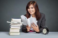 Asiatische Geschäftsfrau, die viele Bücher und Lächeln liest Lizenzfreie Stockfotografie
