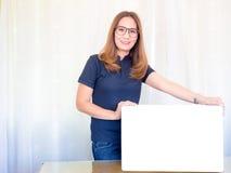Asiatische Geschäftsfrau, die weißes Brett im Büro hält lizenzfreies stockfoto