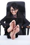 Asiatische Geschäftsfrau mit Füßen oben auf einem Schreibtisch stockfotografie