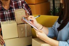 Asiatische Geschäftsfrau-Prüfungsliste des Verpackenpaketes für an Kunden liefern stockbilder