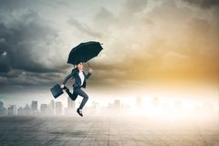 Asiatische Geschäftsfrau springt mit Regenschirm lizenzfreies stockbild
