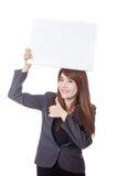 Asiatische Geschäftsfraudaumen-oben halten ein leeres Zeichen obenliegend Stockbilder