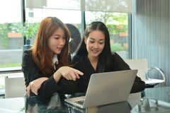Asiatische Geschäftsfrauen, die Laptop im Konferenzzimmer bearbeiten und verwenden stockbild
