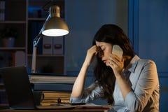 Asiatische Geschäftsfraukopfschmerzen auf dem Smartphone, der über die Zeit hinaus arbeitet Stockfotos