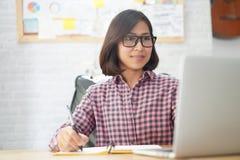 Asiatische Geschäftsfraulesung auf Laptop-Computer lizenzfreie stockbilder