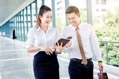Asiatische Geschäftsleute, die außerhalb des Büros gehen und sprechen lizenzfreie stockfotos