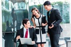 Asiatische Geschäftsleute, die draußen an Laptop arbeiten stockbild