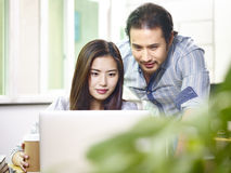 Asiatische Geschäftsleute, die im Büro zusammenarbeiten stockbilder