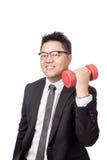 Asiatische Geschäftsmannübung mit einem Dummkopf in seiner Hand Stockfotografie