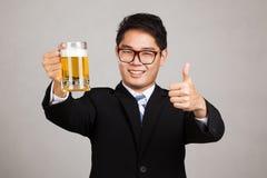 Asiatische Geschäftsmanndaumen oben mit Becher Bier Lizenzfreies Stockfoto