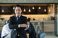 Asiatische Geschäftsmannstellung, lächelnd und schauen zur Kamera Erfolgreiches Konzept des Geschäfts Lizenzfreies Stockbild