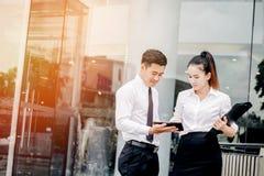 Asiatische Geschäftspaarsitzung unter Verwendung der digitalen Tablette im Freien nachher Lizenzfreie Stockbilder