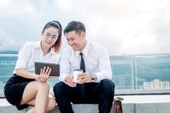 Asiatische Geschäftspaarsitzung unter Verwendung Stands der digitalen Tablette des im Freien stockfoto