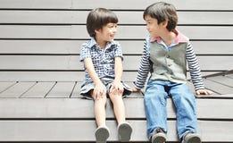 Asiatische Geschwister, die zusammen mit Lächeln sitzen stockfotos