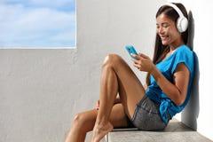 Asiatische gesunde Yogafrau, die auf Kopfhörer hört Lizenzfreies Stockfoto