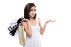Asiatische glückliche lächelnde haltene Einkaufstaschen der Einkaufsfrau lokalisiert auf weißem Hintergrund Lizenzfreies Stockbild