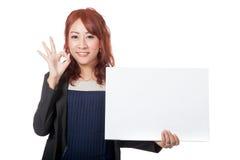 Asiatische glückliche Show des Büromädchens ein leeres Zeichen und OKAYzeichen mit ihrem h Lizenzfreie Stockfotos