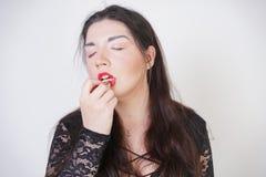 Asiatische gl?ckliche Frau malt ihre Lippen mit Lippenstift auf wei?em Studiohintergrund Falsch versuchen Sie, guter Selbst zu tu stockfotografie