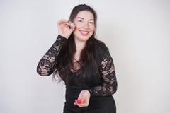 Asiatische gl?ckliche Frau malt ihre Lippen mit Lippenstift auf wei?em Studiohintergrund Falsch versuchen Sie, guter Selbst zu tu lizenzfreies stockbild