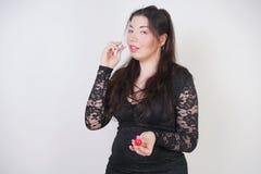 Asiatische gl?ckliche Frau malt ihre Lippen mit Lippenstift auf wei?em Studiohintergrund Falsch versuchen Sie, guter Selbst zu tu stockbilder