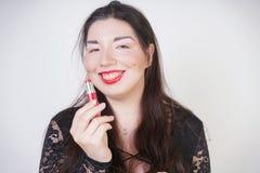 Asiatische gl?ckliche Frau malt ihre Lippen mit Lippenstift auf wei?em Studiohintergrund Falsch versuchen Sie, guter Selbst zu tu stockbild
