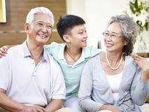 Asiatische Großeltern und Enkelkind des Porträts stockfotos