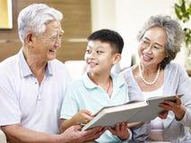 Asiatische Großeltern und Enkelkind, die zusammen ein Buch liest Stockfotografie