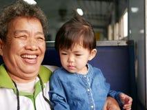 Asiatische Großmutter, die beim Genießen lacht und lächelt, ihre Enkelin halten wie sie zusammen reisend auf einen Zug lizenzfreie stockbilder