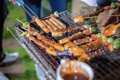 Asiatische Gruppe Freunde, die an Grill und gegrillte shashliks machen stockbild
