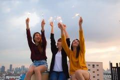 Asiatische Gruppe Freunde, die Wunderkerzen beleuchten und Freiheit bei Sonnenuntergang, asiatische Frau glücklich hält Wunderker stockfotografie