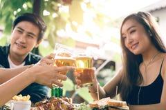 Asiatische Gruppe Teeneger Freunde, die Gläser im Restaurant klirren stockfotografie