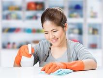Asiatische Hausfrau, die auf Tabelle fegt Lizenzfreies Stockfoto