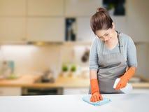 Asiatische Hausfrau, die auf Tabelle fegt Lizenzfreies Stockbild