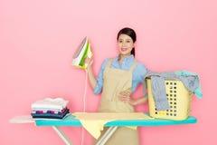 Asiatische Hausfrau, die ein Ausgangsbügeln hält Lizenzfreies Stockfoto