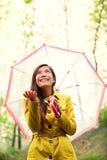 Asiatische Herbstfrau glücklich nach Regen unter Regenschirm Stockfotografie
