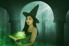 Asiatische Hexenfrau, die das Buch hält Lizenzfreies Stockfoto