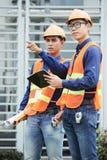 Asiatische Ingenieure, die Abstand auf Baustelle betrachten lizenzfreies stockfoto