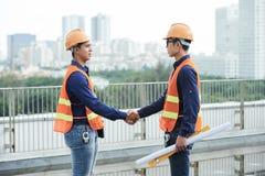 Asiatische Ingenieure, die Hände auf Baustelle rütteln lizenzfreie stockbilder