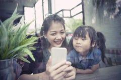 Asiatische jüngere Frau und die Kinder, die zum intelligenten Telefon schauen, sortieren a aus Stockbilder