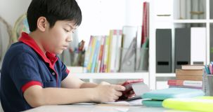 Asiatische Jugendliche, die Ihre Hausarbeit mit Tablet-Computer mit ernstem Gesicht tun stock footage