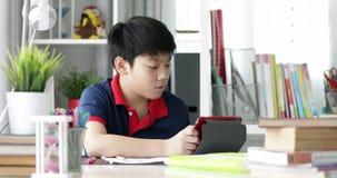 Asiatische Jugendliche, die Ihre Hausarbeit mit Tablet-Computer mit ernstem Gesicht tun stock video