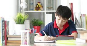 Asiatische Jugendliche, die Ihre Hausarbeit mit Tablet-Computer mit Lächelngesicht tun stock video