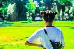 Asiatische Jugendlichen stehen zurück mit einem Gartenhintergrund lizenzfreie stockfotos