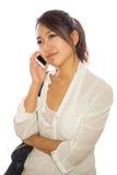 Asiatische junge Frau, die auf Mobiltelefon spricht Stockbilder