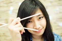 Asiatische junge Frau, die Essstäbchen hält lizenzfreie stockfotografie