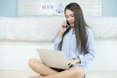 Asiatische junge Frau, die Laptop-Computer und Smartphone in ihrem Schlafzimmer verwendet Konzept zu Hause bearbeiten Lizenzfreies Stockbild