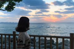 Asiatische junge Frau, die schönen Sonnenuntergang über Horizont aufpasst lizenzfreies stockbild