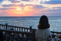 Asiatische junge Frau, die sch?nen Sonnenuntergang ?ber Horizont aufpasst stockfotos