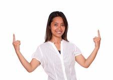 Asiatische junge Frau, die Sie betrachtet und oben zeigt Stockfotografie
